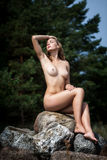 Beautiful nude woman sitting on stones Royalty Free Stock Images