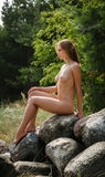 Beautiful nude woman sitting on stones Royalty Free Stock Photography