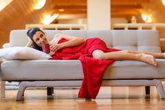 A beautiful nude woman wrapped in a cozy blanket relaxing on the. Sofa in a Loft Apartment Royalty Free Stock Photo