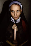 Beautiful nun with a candle reading the Bible. religious concept Stock Photography
