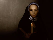 Beautiful nun with a candle reading the Bible. religious concept Stock Photos