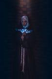 Beautiful nun stand in shaft of lights. Near brick wall Stock Photo