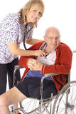 Beautiful nurse checking elderly patient. Isolated on white Royalty Free Stock Image