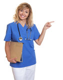 Beautiful nurse with curly blonde hair and medical file pointing sideways Royalty Free Stock Photos