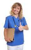 Beautiful nurse with curly blonde hair and medical file showing thumb Stock Photos