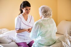 Beautiful nurse holding hand of old senior patient and comfort h. Er at nursing home stock photo