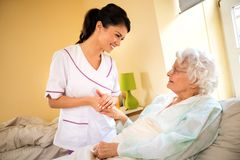 Beautiful nurse holding hand of old senior patient and comfort h. Er at nursing home Stock Photography