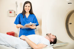 Beautiful nurse next to a CT scanner royalty free stock image