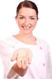 Beautiful nurse offering pills and smiling Stock Photography
