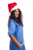 Beautiful nurse or surgeon with Christmas hat. Beautiful brunette female nurse or surgeon with a Christmas hat wearing a blue uniform royalty free stock photos