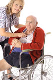Beautiful nurse taking care of elderly patient. Isolated on white Royalty Free Stock Photos