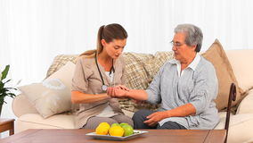 Beautiful nurse taking the pulse of her patient at home Stock Image