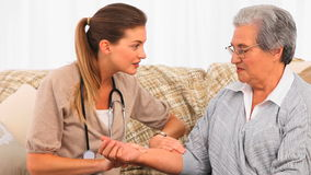 Beautiful nurse taking the pulse of her patient at home Stock Photo
