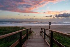 Beautiful ocean beach entrance at sunrise. Sunrise ocean beach. Sea beach wooden walkway, path entrance. Sandy ocean beach on sunrise, sunset Stock Images