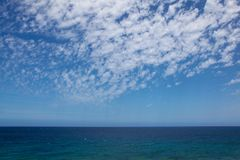 Ocean and the blue skies. Beautiful ocean with blue skies and composition of nice clouds on a sunny day stock photo