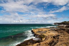 Beautiful ocean scene. Tropical ocean waters flowing on to the rocky shore Stock Photography