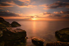 Beautiful ocean sunrise - calm sea and boulders stone coastline. With unusual light Royalty Free Stock Image