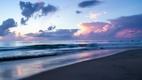 Beautiful ocean sunrise and gentle waves as the morning sun lights the clouds and reflects on the surface of the sea and wet sand. royalty free stock photo