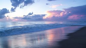 Beautiful ocean sunrise and gentle waves as the morning sun lights the clouds and reflects on the surface of the sea and wet sand. royalty free stock image