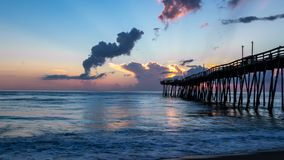 Beautiful ocean sunrise and gentle waves beside an old wooden fishing pier extending far out into the sea. Dramatic sky. Sunrise shines on the tall white clouds royalty free stock photography