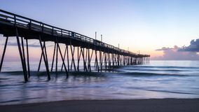Beautiful ocean sunrise and gentle waves beside an old wooden fishing pier extending far out into the sea. Sunrise shines on the tall white clouds and the calm royalty free stock photography