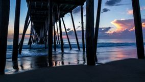 Beautiful ocean sunrise and gentle waves seen from beneath a wooden fishing pier. stock image