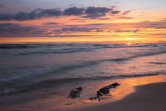 Beautiful ocean sunset at the beach with a plastic bag in the sand Royalty Free Stock Images