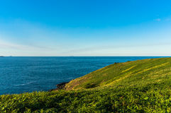 Beautiful ocean view and green grassy hill with. Clear sky on the background with space for text. Coffs Harbour, Australia Royalty Free Stock Photography