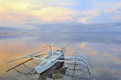 Beautiful ocean view at sunrise. Outrigger boat on beautiful calm ocean at sunrise, Panglau Island, Philippines Royalty Free Stock Images