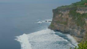 Beautiful ocean waves. Aerial top view of Tropical beach Bali, Indonesia. Ocean waves breaking on the stone cliffs. Aerial top view of Tropical beach Bali stock video