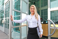 A beautiful office lady opening a door Royalty Free Stock Photography