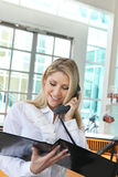 Beautiful office lady talking on the phone and checking profile Stock Photography