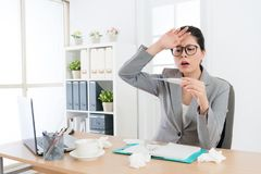 Beautiful office worker lady using thermometer Royalty Free Stock Image