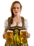 Beautiful Oktoberfest server serving beer. Photo of a beautiful female waitress wearing traditional dirndl and holding huge beers over white background Stock Photography