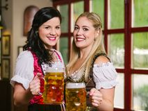 Beautiful Oktoberfest waitresses with beer. Photo of two beautiful female waitresses wearing traditional dirndl and holding huge beers in a pub Stock Photos