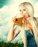 Beautiful oktoberfest young sexy woman. Wearing a dirndl drink beer from mug outdoor Stock Image