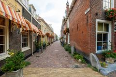 Beautiful old alley with flowers in the old city center of Delft, the royalty free stock photos