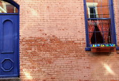 Beautiful old brick wall with blue door and window Stock Photos