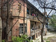 Beautiful old brown dilapidated three-story house with windows and balconies, slum terraces in the old urban area of Tbilisi. stock photography