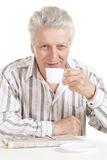 Beautiful old Caucasian man with cup sits Stock Photo