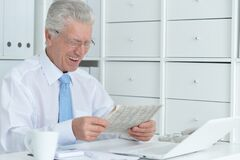 Free Beautiful Old Caucasian Man With Laptop Reading Newspaper Royalty Free Stock Photography - 181671117