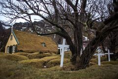 Beautiful old cemetery, graves covered with grass. Green grass- covered graveyard, small church in the background, black tree, white crosses Stock Photography