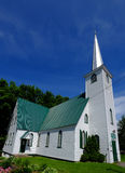 Beautiful old church in Quebec. Green-roofed white church with tall steeple in Quebec Royalty Free Stock Image