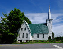 Beautiful old church in Quebec. Green-roofed white church with tall steeple in Quebec Stock Photography