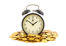 Beautiful old clock staying on one golden coins. Royalty Free Stock Photography