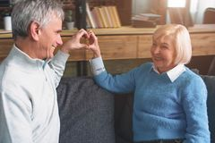 Beautiful old couple are sitting together on the couch and keepi stock photos