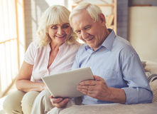 Beautiful old couple. Is using a digital tablet and smiling while sitting on couch at home stock photography