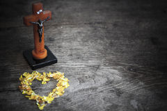 Beautiful old cross with jesus and heart from leafs on the old wooden floor Royalty Free Stock Photo