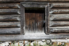 Beautiful old door on the wooden wall of the old house. Excellent background. Stock Photo