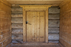 Beautiful old door on the wooden wall of the old house. Excellent background. Royalty Free Stock Images